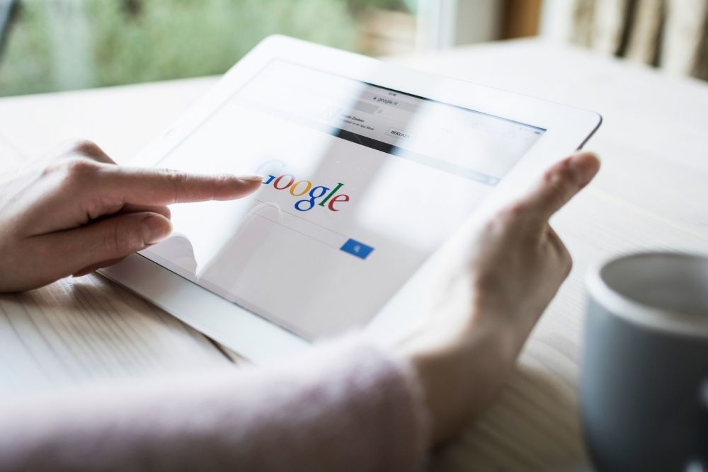Person using tablet to search Google